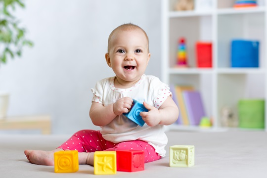 A baby toddler playing with toys at home.